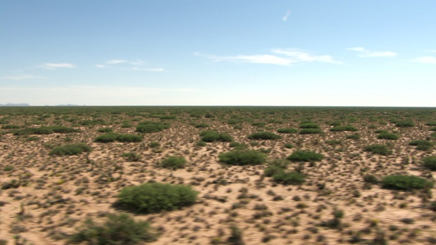 A view across a wide desert plain in New Mexico Aerial Stock Footage | AF0001_000909