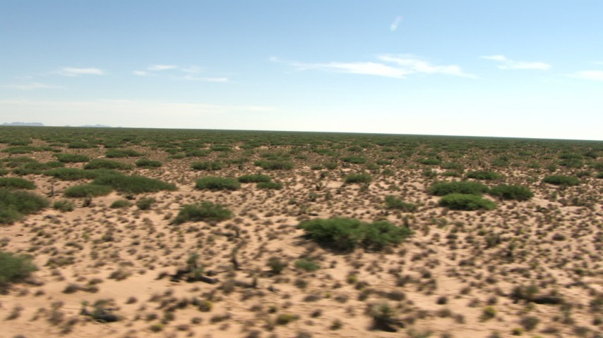 Fly low past a desert plain, New Mexico Aerial Stock Footage | AF0001_000910