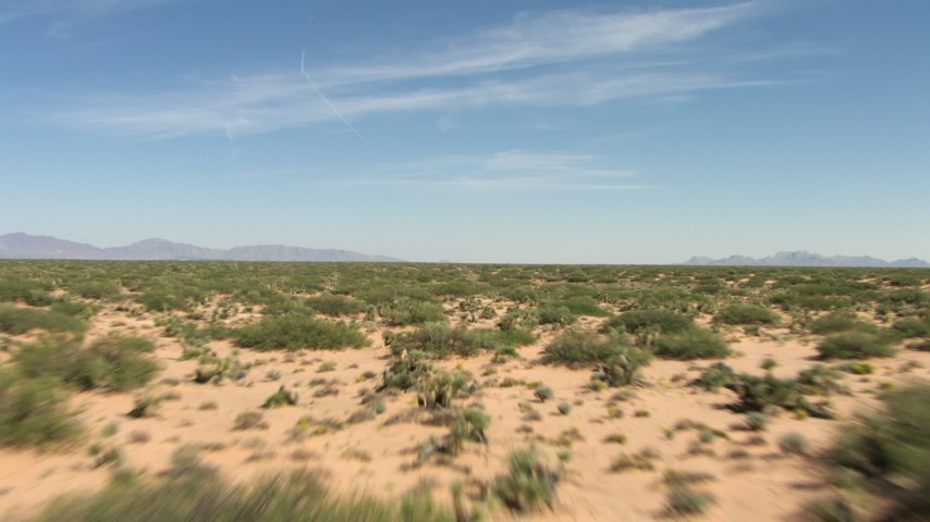 An arid desert plain with vegetation in New Mexico Aerial Stock Footage | AF0001_000913
