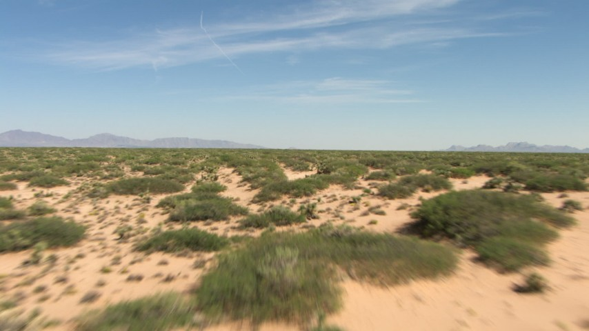 Desert vegetation on an arid plain, distant mountains, New Mexico Aerial Stock Footage | AF0001_000914