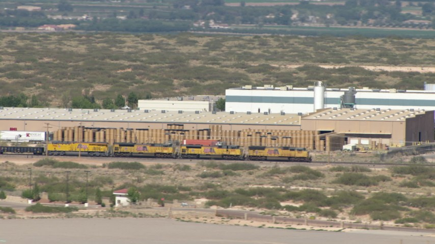 HD stock footage aerial video of a train cruising past warehouse buildings in El Paso, Texas Aerial Stock Footage | AF0001_000920