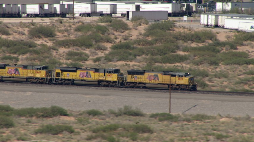 HD stock footage aerial video of a train passing by many parked semi-trailers, El Paso, Texas Aerial Stock Footage | AF0001_000921