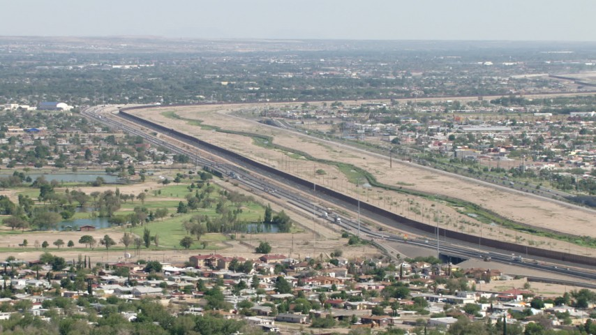 The US/Mexico border fence by 375 freeway and golf course, El Paso, Texas Aerial Stock Footage AF0001_000942