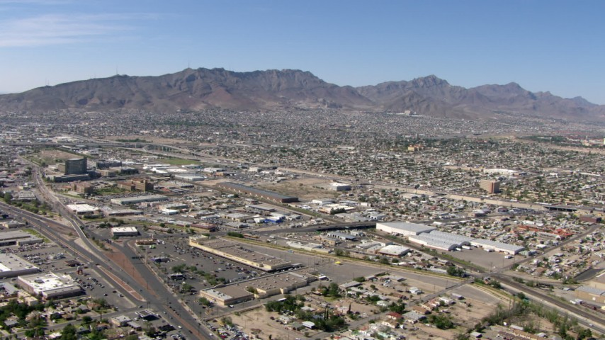Fox Plaza shopping center, warehouse buildings, and neighborhoods near the Franklin Mountains in El Paso, Texas Aerial Stock Footage AF0001_000945 | Axiom Images