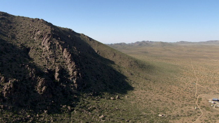 HD stock footage aerial video fly around a jagged mountain slope beside a dry plain near El Paso, Texas Aerial Stock Footage | AF0001_000951