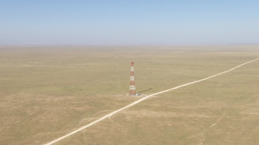 Approach a tower by a dirt road in a desert plain near El Paso, Texas Aerial Stock Footage | AF0001_000960