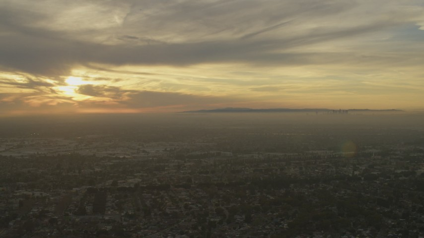 Urban neighborhoods and Downtown Los Angeles skyline seen from Santa Fe Springs, California at sunset Aerial Stock Footage | AF0001_000976