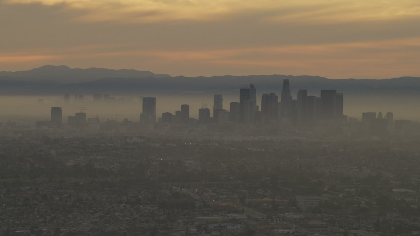 The Downtown Los Angeles skyline at a hazy sunset, California  Aerial Stock Footage AF0001_000984