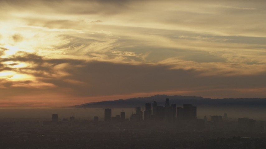5K stock footage aerial video of sunset-lit clouds above the Downtown Los Angeles skyline in haze, California Aerial Stock Footage | AF0001_000987