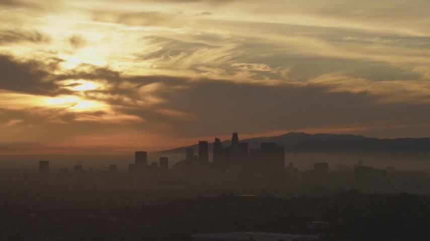 5K stock footage aerial video of a view of sunset and clouds above the hazy Downtown Los Angeles skyline, California Aerial Stock Footage | AF0001_000988