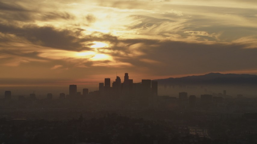 5K stock footage aerial video of the sunset and clouds over the hazy Downtown Los Angeles skyline, California Aerial Stock Footage | AF0001_000989