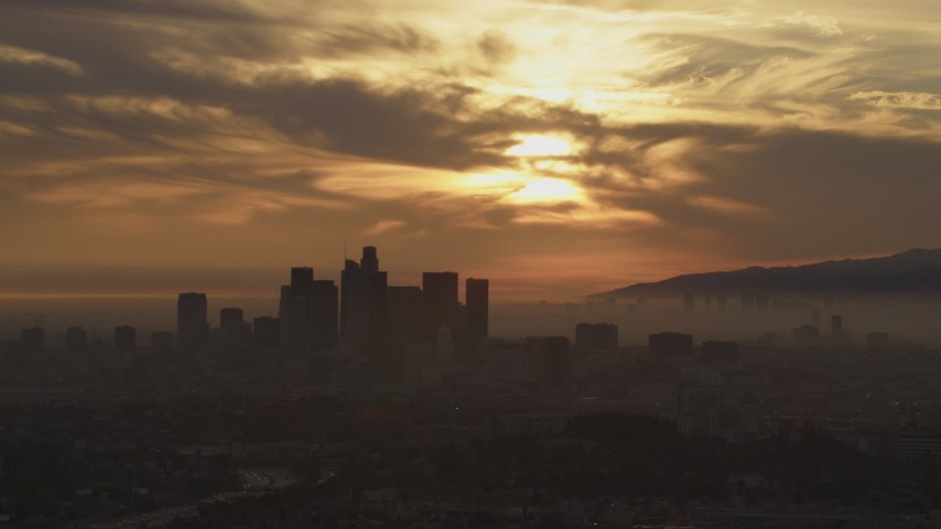 5K stock footage aerial video of passing the hazy Downtown Los Angeles skyline at sunset, California Aerial Stock Footage | AF0001_000990