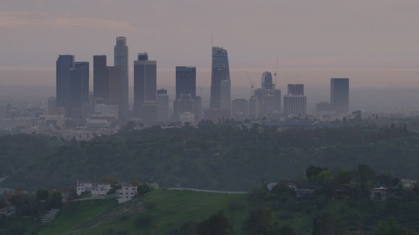 Downtown Los Angeles skyline seen while flying behind Dodger Stadium at twilight, California  Aerial Stock Footage | AF0001_000998