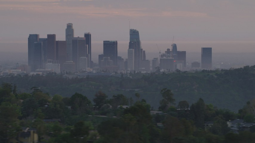5K stock footage aerial video of Downtown Los Angeles skyline seen while flying behind green hills and Dodger Stadium at twilight, California Aerial Stock Footage | AF0001_000999