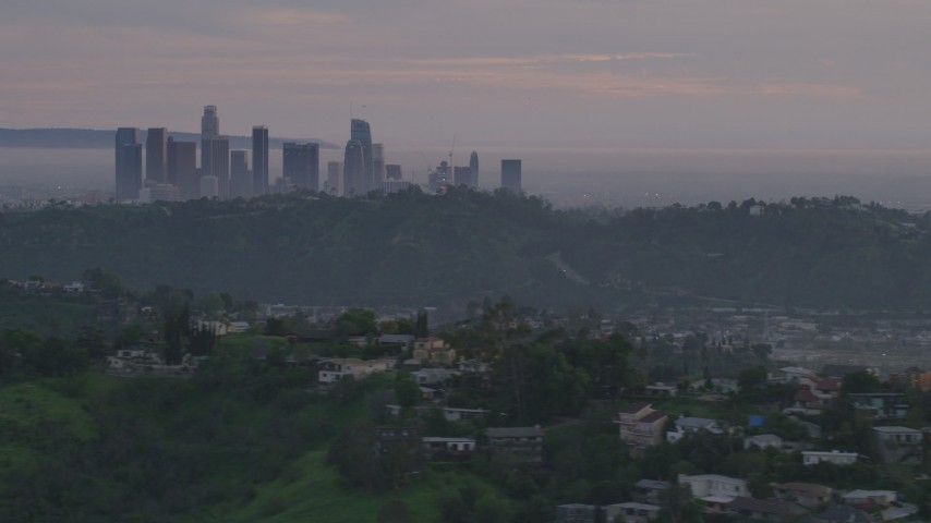 5K stock footage aerial video of Downtown Los Angeles skyline seen while flying by hillside homes at twilight, California Aerial Stock Footage | AF0001_001000