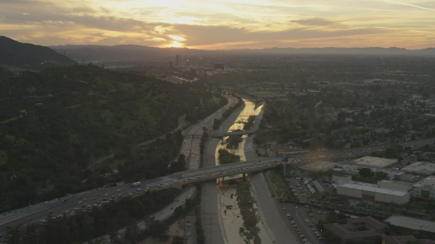 5K stock footage aerial video of heavy traffic on 134 and I-5 by the Los Angeles River and neighborhoods at sunset, Burbank, California Aerial Stock Footage | AF0001_001007