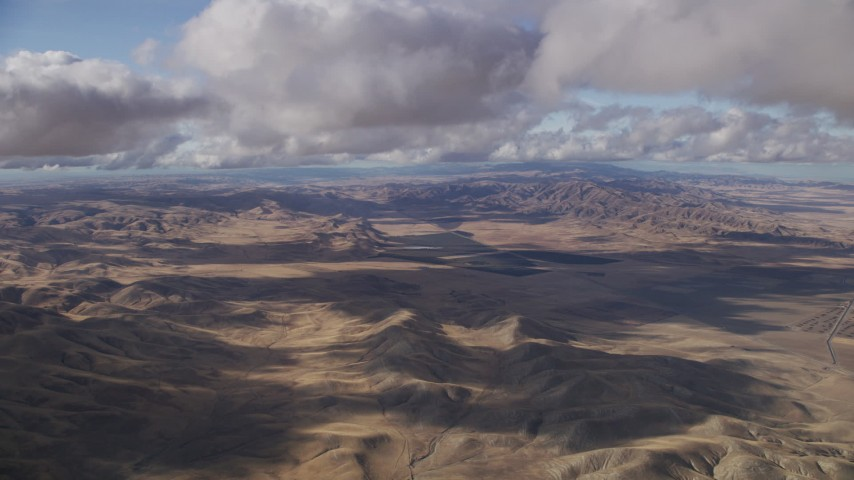 Fly over desert hills beneath clouds in Southern California Aerial Stock Footage | AF0001_001020