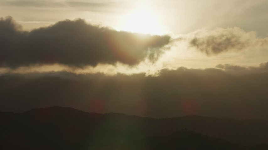 Setting sun behind clouds and mountain ridges in Southern California Aerial Stock Footage | AF0001_001031
