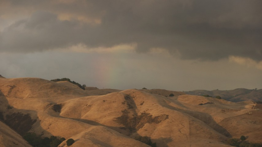 8K stock footage aerial video of a rainbow behind brown mountains at sunset in Northern California Aerial Stock Footage | AF0001_001033