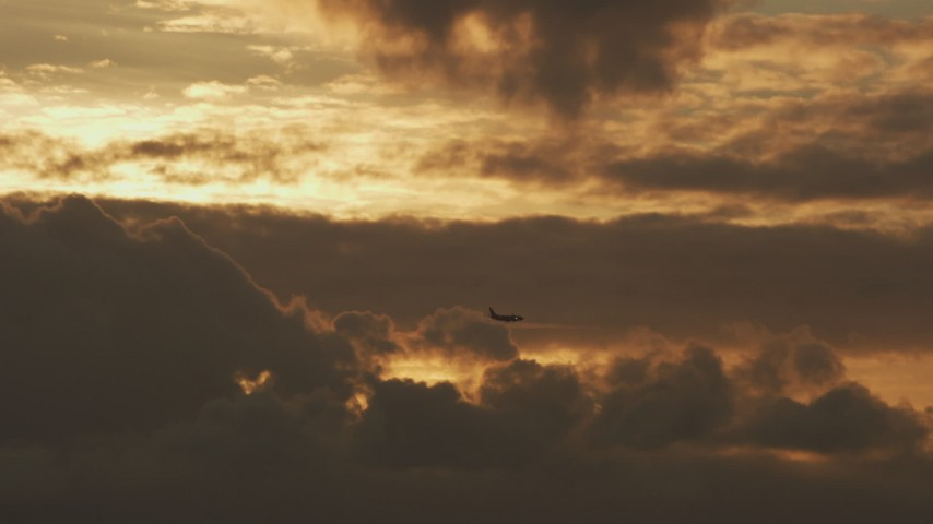 Track an airliner descending from the clouds at sunset in Northern California Aerial Stock Footage AF0001_001037