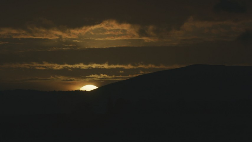 The setting sun disappearing behind a mountain ridge in Northern California Aerial Stock Footage | AF0001_001045