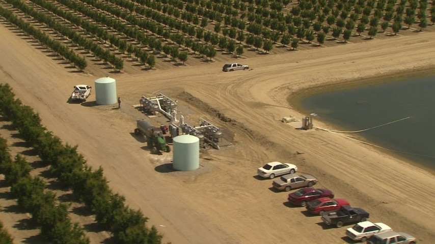1080 stock footage aerial video flying by tractor pulling tank near crops, manmade pond, Central Valley, California Aerial Stock Footage | AI06_FRM_033