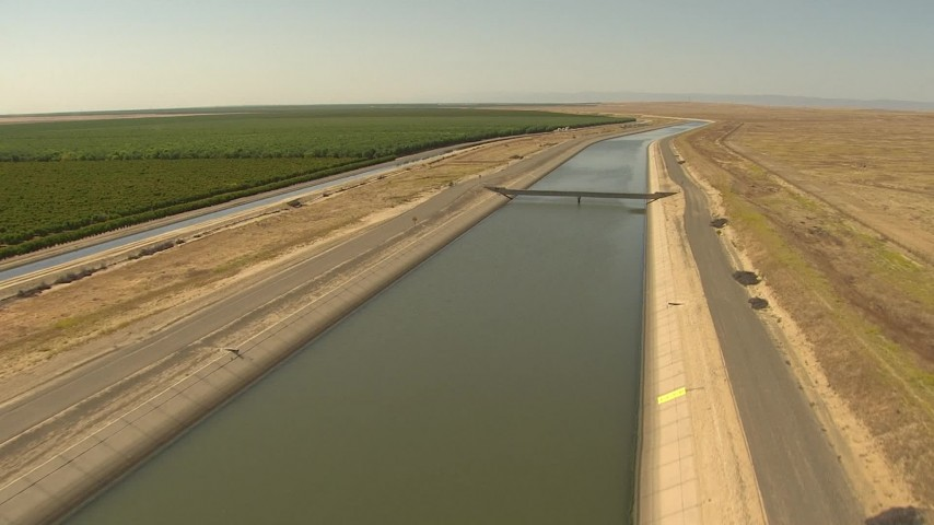 1080 stock footage aerial video flying low over aqueduct, pan to orchards, Central Valley, California Aerial Stock Footage | AI06_FRM_064