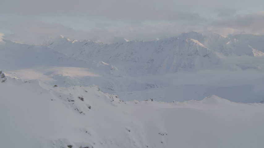 4K stock footage aerial video reveal snow-covered Chugach Mountains, clouds, Chugach National Forest, Alaska Aerial Stock Footage | AK0001_0009
