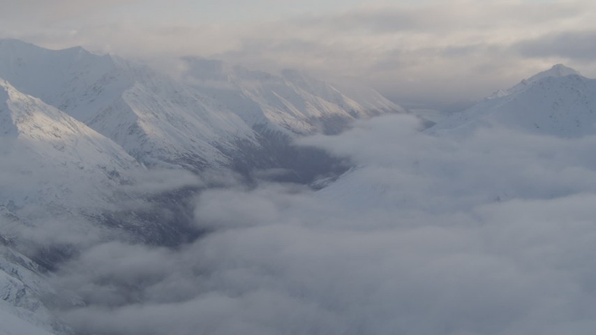 4K stock footage aerial video valley between snow covered peaks, low clouds, Chugach National Forest, Alaska Aerial Stock Footage   AK0001_0012