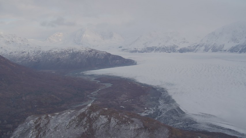 4K stock footage aerial video pan right by Knick Glacier, bordered by Chugach Mountains, Knik Glacier, Alaska Aerial Stock Footage | AK0001_0025