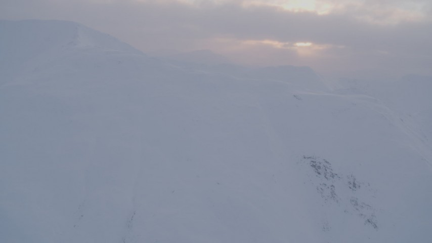 4K stock footage aerial video approaching snowy peaks, low clouds, Chugach Mountains, Alaska, sunset Aerial Stock Footage | AK0001_0078