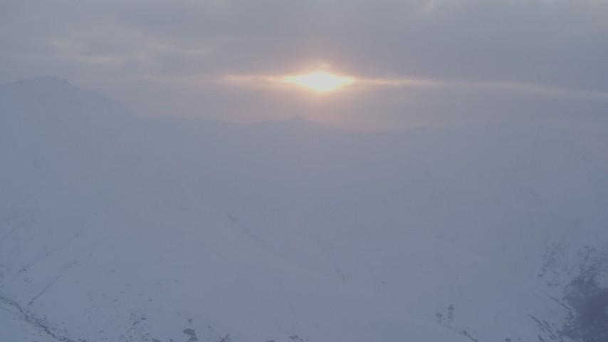 4K stock footage aerial video approaching sun peeking through low clouds, Chugach Mountains, Alaska, sunset Aerial Stock Footage | AK0001_0081