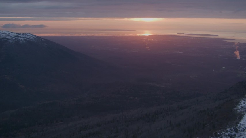 4K stock footage aerial video snow covered slope, revealing Anchorage, Chugach Mountains, Alaska, sunset Aerial Stock Footage | AK0001_0094
