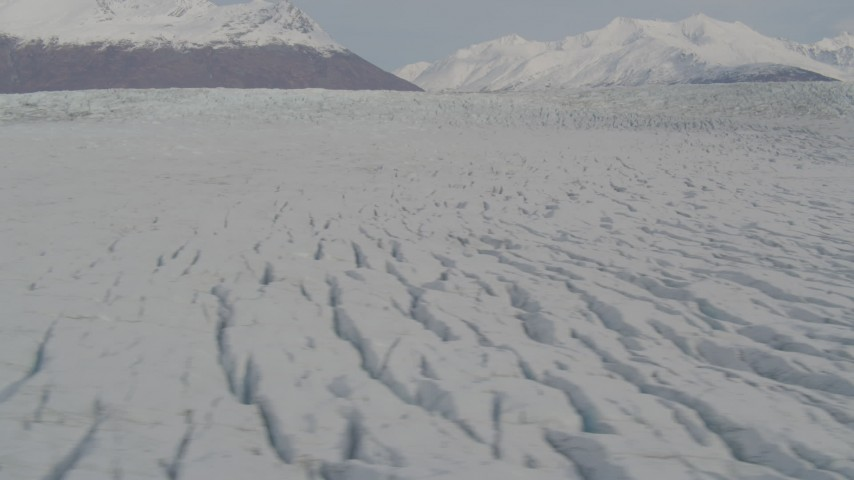 4K stock footage aerial video fly over surface of Knik Glacier, reveal Chugach Mountains, Knik Glacier, Alaska Aerial Stock Footage | AK0001_0142