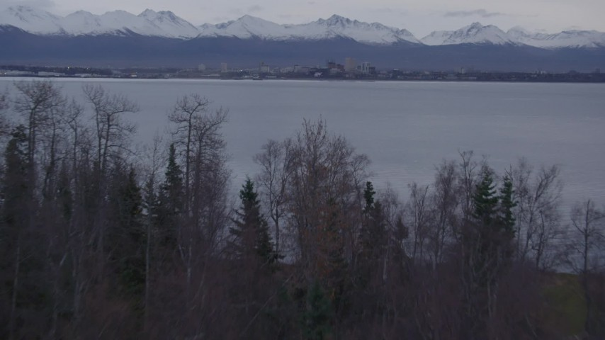 4K stock footage aerial video over wooded shoreline, reveal Downtown Anchorage, Point MacKenzie, Alaska Aerial Stock Footage | AK0001_0173