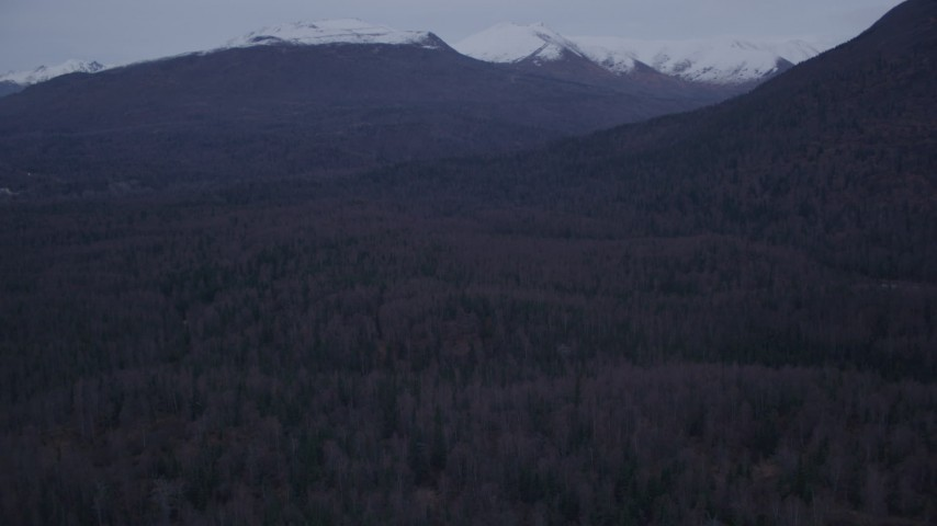 4K stock footage aerial video descending over forested hills, approaching Chugach Mountains, Alaska, twilight Aerial Stock Footage | AK0001_0185