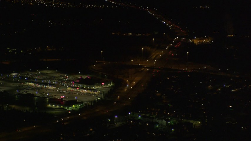 4K stock footage aerial video flying by shopping center, tilt up following Glenn Highway, Anchorage, Alaska, night Aerial Stock Footage | AK0001_0199