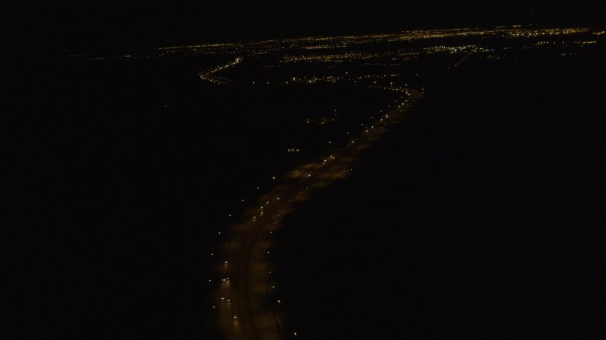 4K stock footage aerial video following Glenn Highway, tilt up to Anchorage, Alaska, night Aerial Stock Footage | AK0001_0203