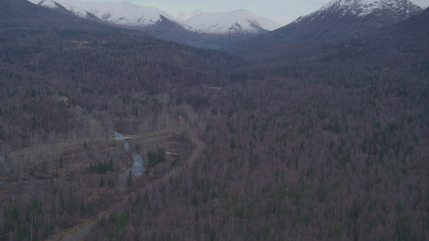 4K aerial video fly over forested foothills, reveal Chugach Mountains, Fort Richardson, Anchorage Aerial Stock Footage | AK0001_0248