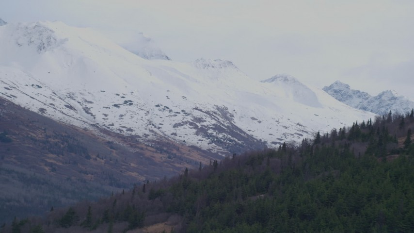 4K stock footage aerial video flying around a slope, revealing snow capped peaks, Chugach Mountains, Alaska Aerial Stock Footage | AK0001_0251