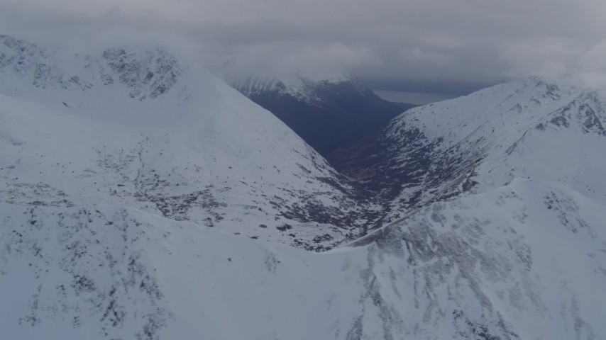 4K stock footage aerial video flying along snowy range, valley in the distance, Chugach Mountains, Alaska Aerial Stock Footage   AK0001_0260
