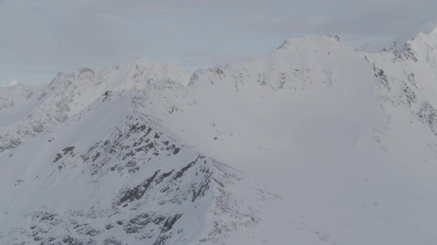4K stock footage aerial video flying along a snowy ridge, approaching a summit, Chugach Mountains, Alaska Aerial Stock Footage | AK0001_0272