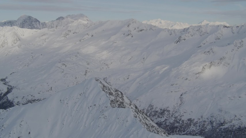 4K aerial video tilt down on summit, revealing a deep valley, Chugach Mountains, Alaska Aerial Stock Footage | AK0001_0276