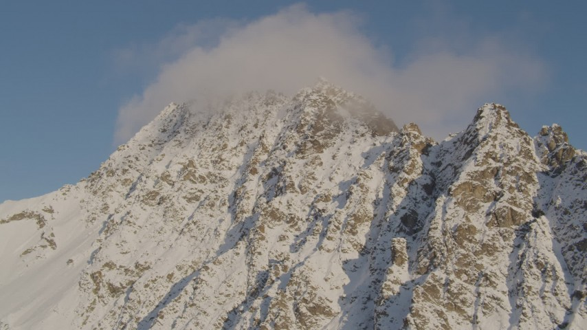 4K aerial video flying by snow covered peak, capped with clouds, Chugach Mountains, Alaska Aerial Stock Footage | AK0001_0294