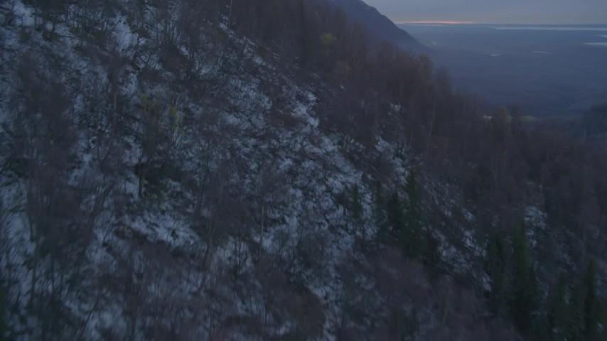 4K stock footage aerial video wooded slope, valley, Eklutna Lake, snowy Chugach Mountains, Alaska, twilight Aerial Stock Footage | AK0001_0316