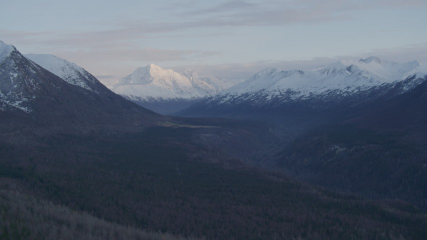 4K stock footage aerial video flying by valley bordered by snowy Chugach Mountains, Alaska, twilight Aerial Stock Footage | AK0001_0317