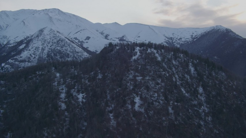4K aerial video fly over wooded summit, approaching snowy Chugach Mountains, Alaska, twilight Aerial Stock Footage   AK0001_0319