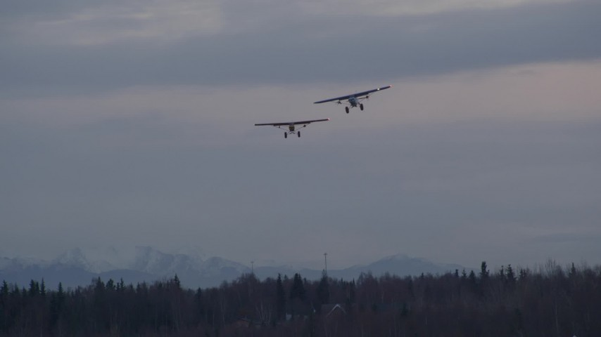 4K stock footage aerial video two planes approaching camera, veering left, Anchorage, Alaska, twilight Aerial Stock Footage | AK0001_0335