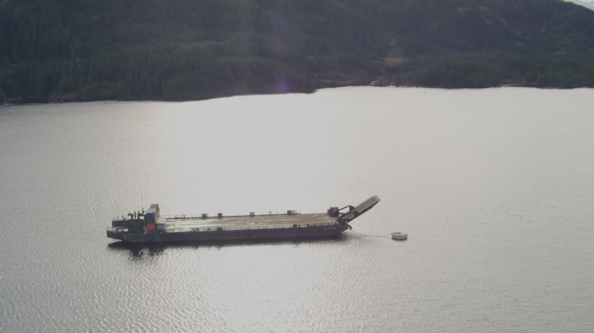 4K stock footage aerial video approaching an anchored barge, reveal surrounding foothills, Shotgun Cove, Alaska Aerial Stock Footage | AK0001_0404