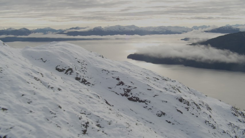 4K stock footage aerial video flying along snowy slope, reveal low clouds over bay, Prince William Sound, Alaska Aerial Stock Footage | AK0001_0420